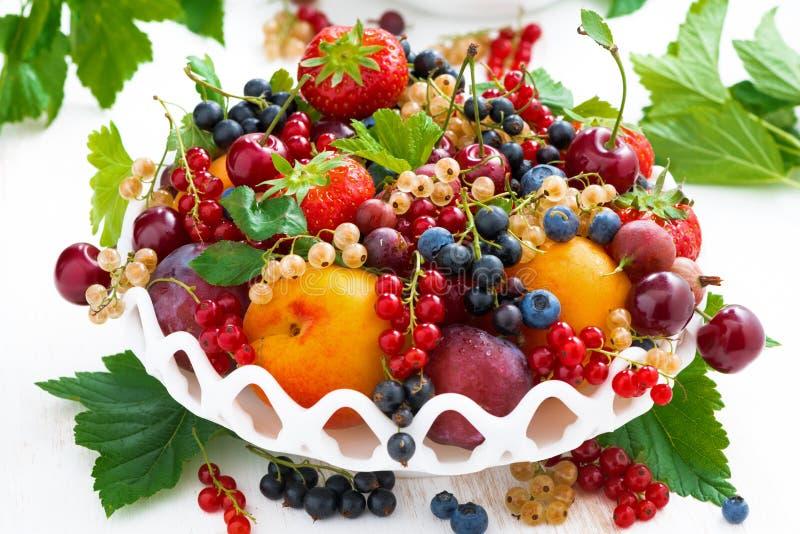 Schotel met verschillende verse seizoengebonden vruchten en bessen op wit stock foto