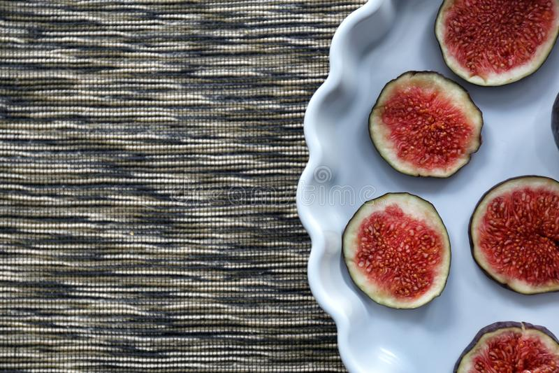 Schotel met verse rijpe fig.plakken op servet royalty-vrije stock afbeeldingen
