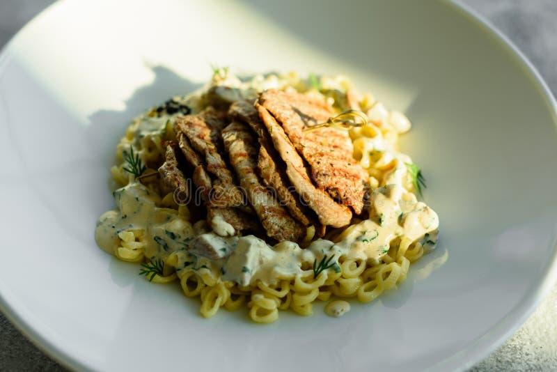 Schotel met vleesstukken, deegwaren, greens en saus van een foiegras royalty-vrije stock afbeeldingen