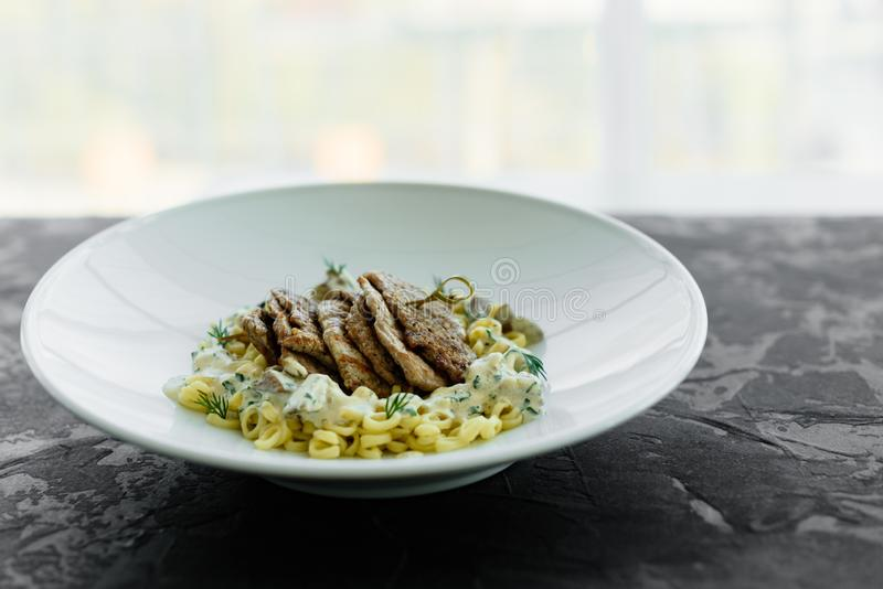 Schotel met vleesstukken, deegwaren, greens en saus van een foiegras royalty-vrije stock foto