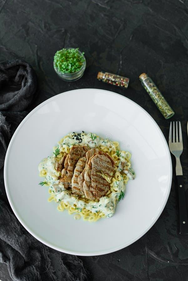 Schotel met vleesstukken, deegwaren, greens en saus van een foiegras royalty-vrije stock foto's