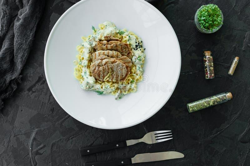 Schotel met vleesstukken, deegwaren, greens en saus van een foiegras stock afbeelding