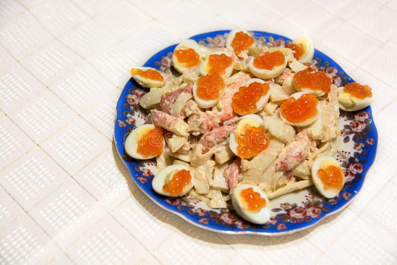 Schotel met zeevruchtensalade Zalmkuiten en eieren stock foto