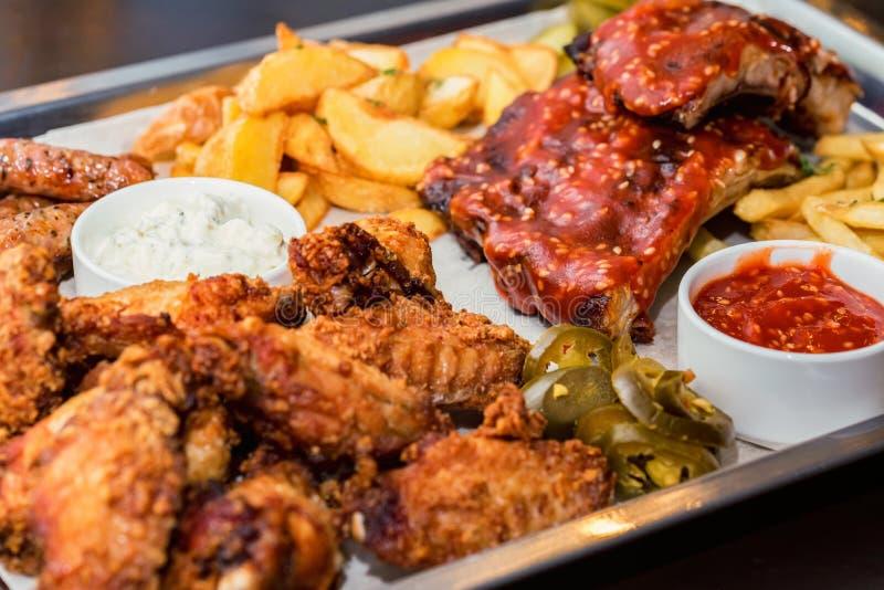 Schotel van gemengd vlees Geroosterde ribben, kippenvleugels en worsten met Frieten royalty-vrije stock foto