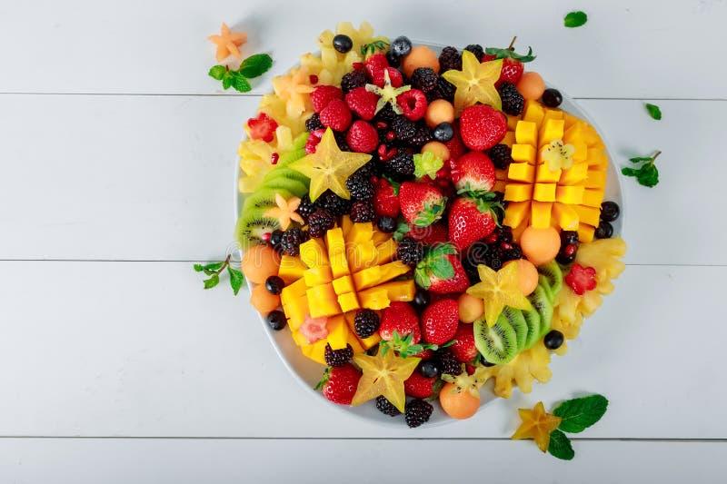 Schotel van mango, sinaasappelen, kiwi Aardbeien, bosbessen meloen druiven, kiwi starfruit op de witte lijst royalty-vrije stock fotografie