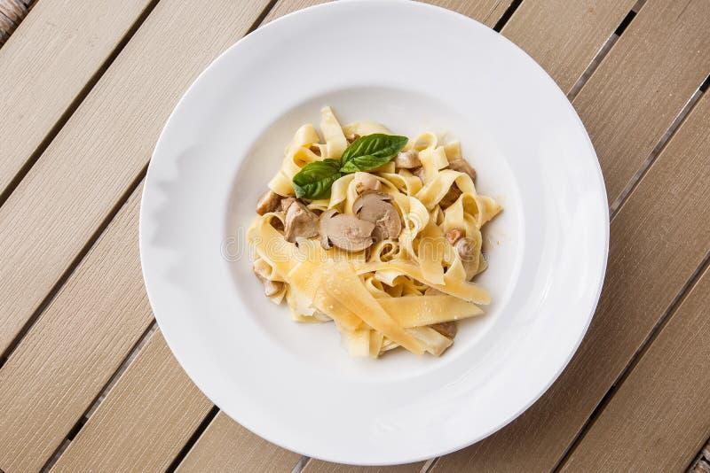 Schotel van tagliatelle de vegetarische Deegwaren met Paddestoelen die met basilicum worden verfraaid Heerlijke lunch met deegwar royalty-vrije stock fotografie