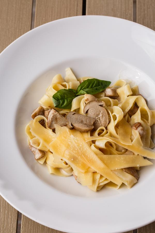 Schotel van tagliatelle de vegetarische Deegwaren met Paddestoelen die met basilicum worden verfraaid Heerlijke lunch met deegwar stock afbeeldingen