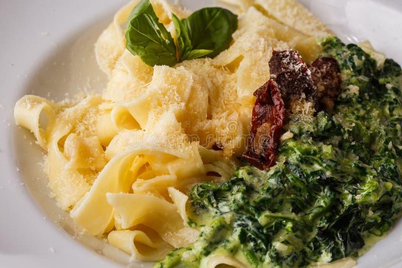 Schotel van tagliatelle de vegetarische Deegwaren met spinazie en droge die tomaten met basilicum wordt verfraaid Heerlijke lunch stock afbeeldingen