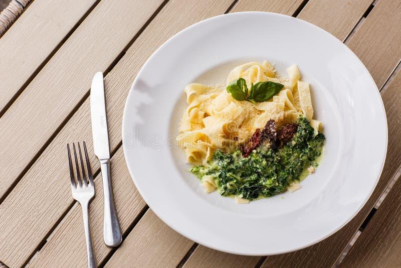 Schotel van tagliatelle de vegetarische Deegwaren met spinazie en droge tomaten die met basilicum wordt verfraaid Heerlijke lunch royalty-vrije stock foto