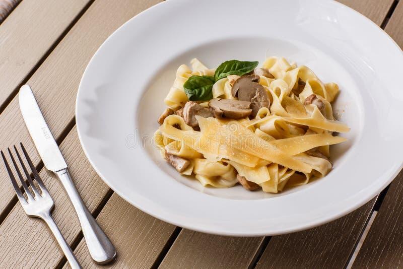 Schotel van tagliatelle de vegetarische die Deegwaren met Paddestoelen met basilicum worden verfraaid Heerlijke lunch met deegwar stock foto