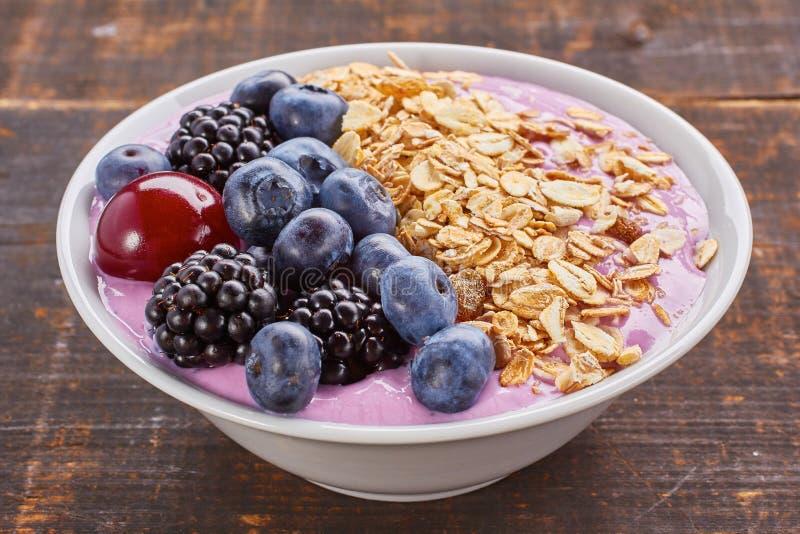 Schotel van yoghurt smoothie, verse bessen en muesli stock foto