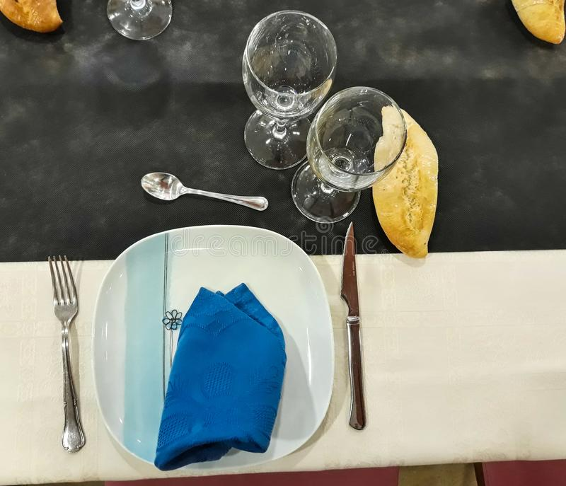Schotels en bestek op de eettafel worden voorbereid die royalty-vrije stock foto's