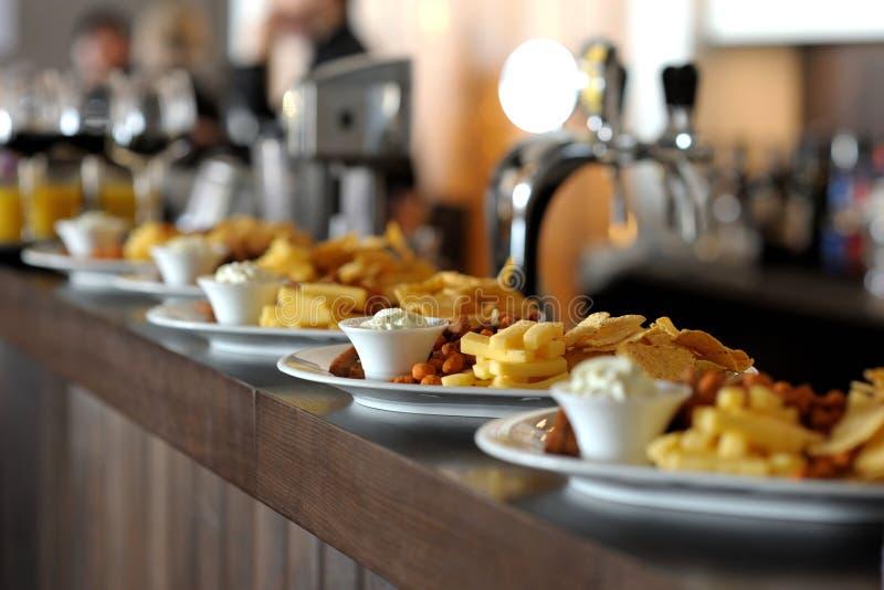 Schotels met snacks op staafteller stock afbeelding