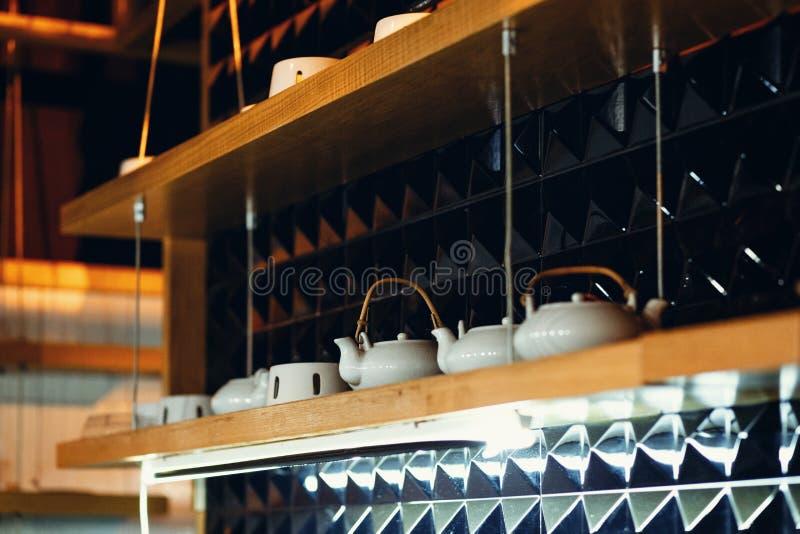 Schotels op de planken in het restaurant op een donkere achtergrond stock foto's