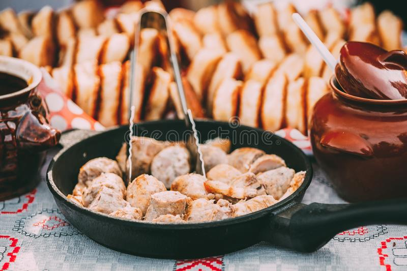 Schotels van de traditionele Witrussische keuken - gebraden bacon en vleesworsten, gebakjes stock afbeeldingen