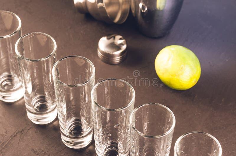 Schoten klaar voor alcohol op bar/schoten klaar voor alcohol en kalk op bar stock foto's
