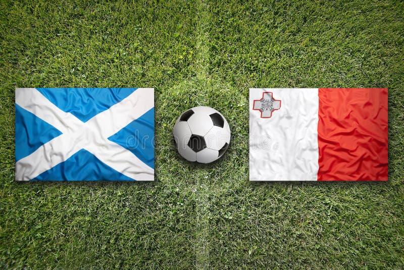 Schotland versus De vlaggen van Malta op voetbalgebied stock fotografie