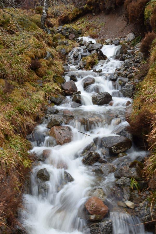 Schots watervalwater die over rotsen draperen royalty-vrije stock afbeeldingen