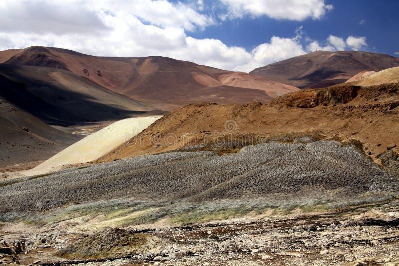 Schotterweg, der durch unwirkliche trockene unfruchtbare Landschaft zu Copiapo in Atacama-Wüste, Chile führt stockbild