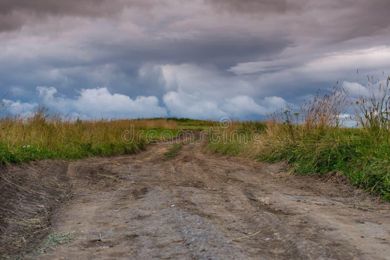 Schotterweg, der zu die Spitze des Hügels, drastische Sturmwolken an der Sommerzeit führt stockfotografie