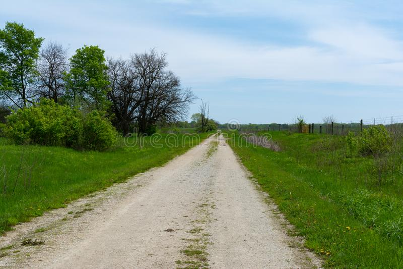 Schotterweg durch das Grasland stockfotografie