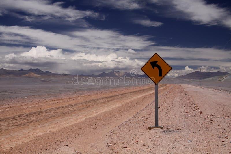 Schotterweg in Endlessness von Atacama-Wüste - gelbes Verkehrszeichen, das linke Richtung, Chile zeigt lizenzfreies stockfoto