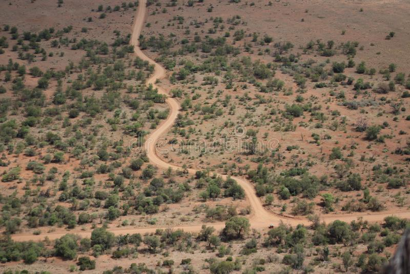 Schotterwegwicklung durch trockene Landschaft stockbild