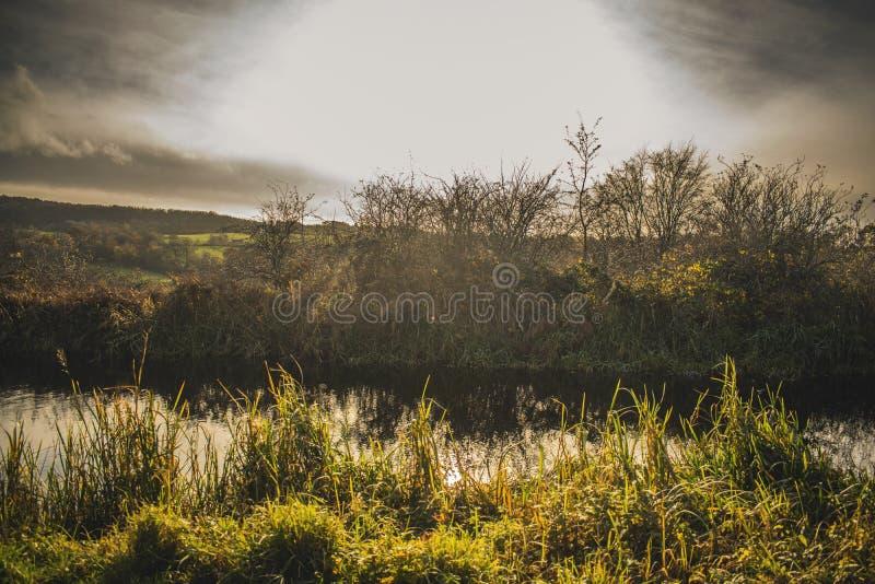 Schottische drastische Himmel-Landschaft mit Fluss-Gras und starker Sonne lizenzfreies stockfoto