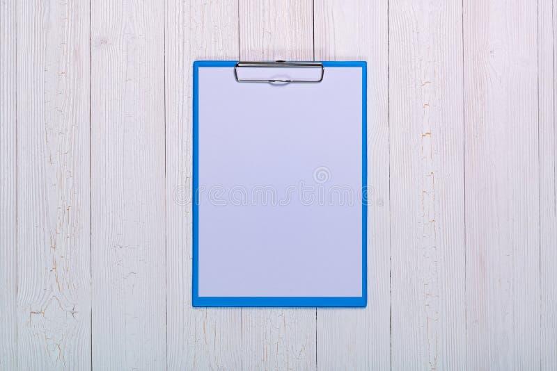 schowek z pustym białego papieru prześcieradłem na drewnianych stołowych odgórnego widoku wi obraz stock