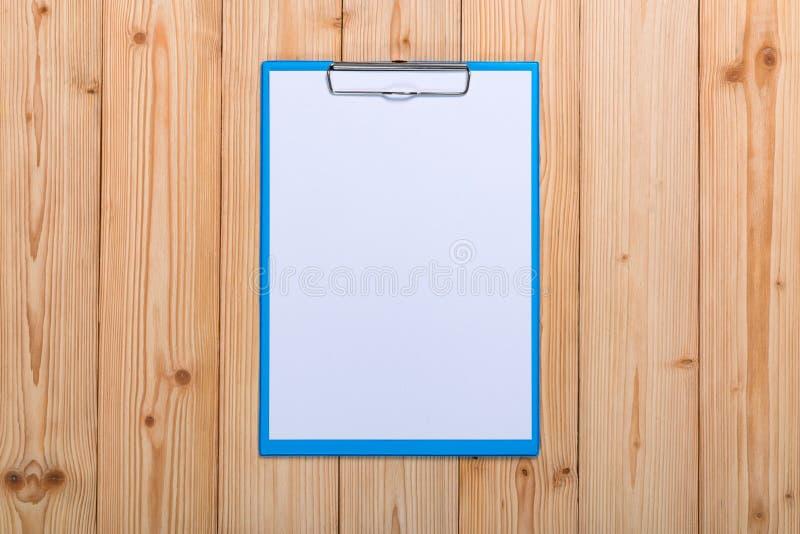 schowek z pustym białego papieru prześcieradłem na drewnianych stołowych odgórnego widoku wi zdjęcia stock