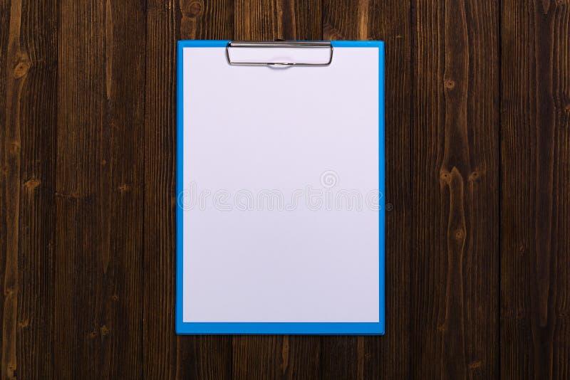 schowek z pustym białego papieru prześcieradłem na drewnianych stołowych odgórnego widoku wi obraz royalty free