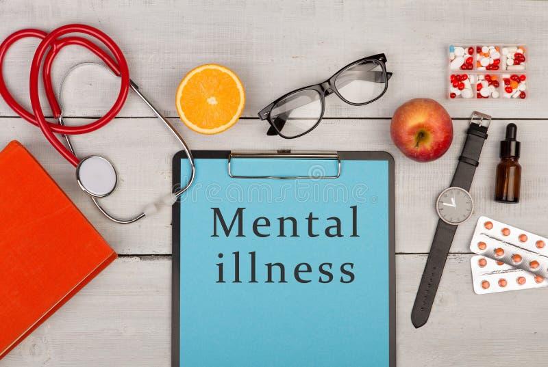 schowek z tekstem & x22; Umysłowy illness& x22; , pigułki, książka, eyeglasses, zegarek i stetoskop, zdjęcie royalty free