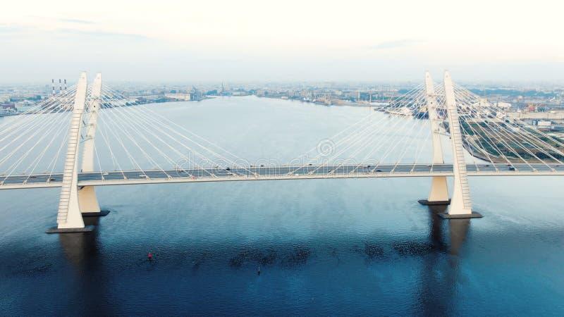 Schrägseilbrücke und Autos, die gegen Stadtbild beschleunigen stockfoto