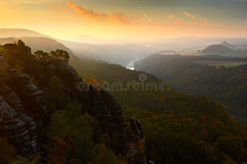 Schrammsteine, schöne Abendansicht über Sandsteinklippe in tiefes nebelhaftes Tal in Sachsen die Schweiz, nebeliger Hintergrund,  stockfotografie