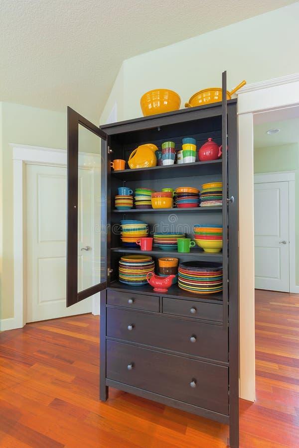 Schrank mit buntem Essgeschirr im Haus stockfoto