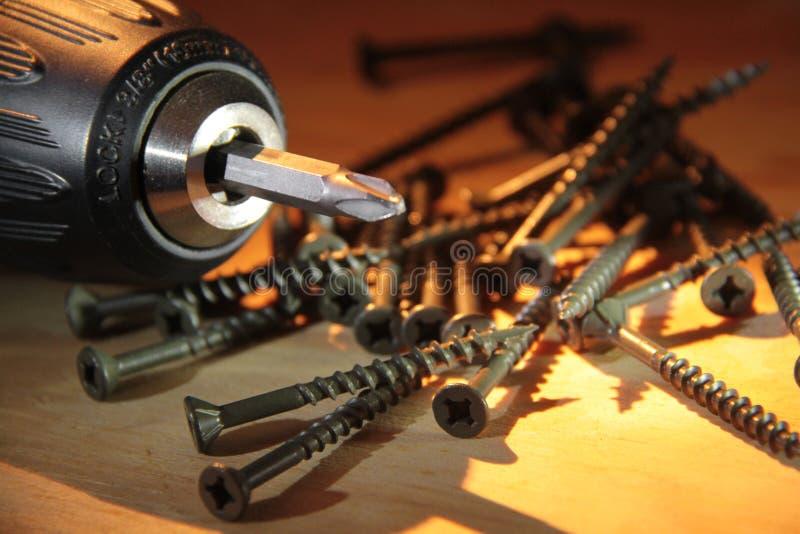 Schrauben des elektrischen Bohrgeräts und des Holzes über Bauholz lizenzfreies stockfoto