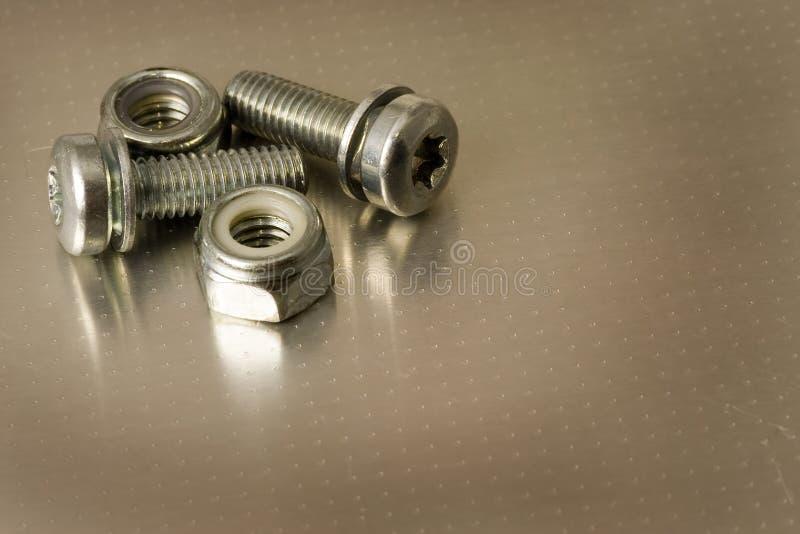 Schrauben und Muttern auf Metall stockbilder