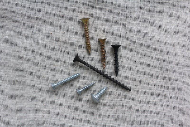 Schrauben von den verschiedenen Längen ausgebreitet auf dem Gewebe stockfotografie