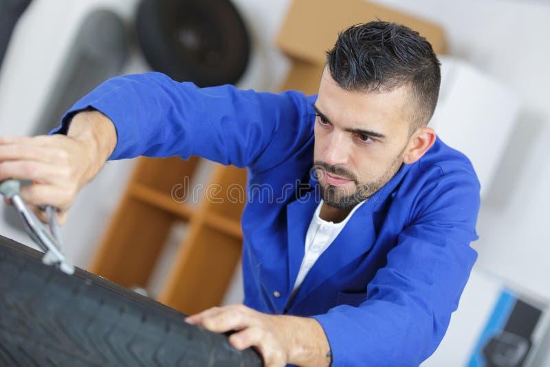 Schraubendes Autorad des Automechanikers durch Schlüssel stockfotografie