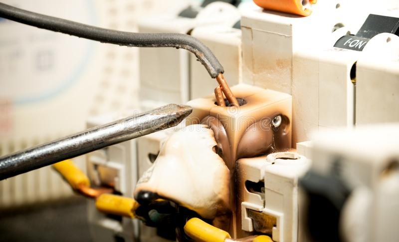 Schraubenzieher, der auf offenen Kupferdraht auf Brand und schmelzender Schalter-Unterbrecher-Sicherung zeigt stockfotos