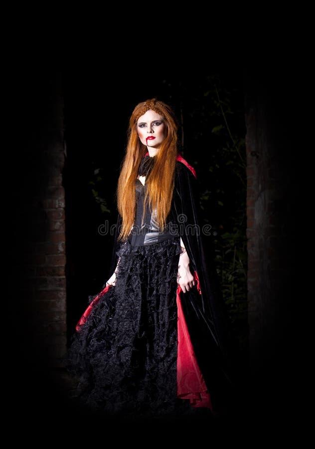 Schreckliche Vampirsfrau im roten Mantel stockfoto