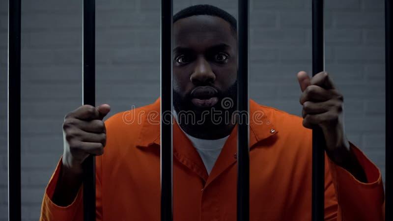 Schrecklicher afro-amerikanischer Gefangener, der Gitter hält, mit Angstkamera lizenzfreie stockfotos