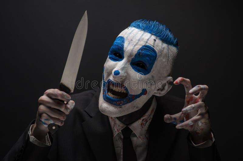 Schrecklicher Clown und Halloween-Thema: Verrückter blauer Clown in einem schwarzen Anzug mit einem Messer in seiner Hand lokalis lizenzfreie stockfotografie