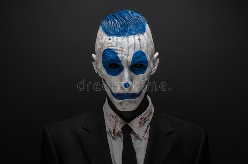 Schrecklicher Clown und Halloween-Thema: Verrückter blauer Clown im schwarzen Anzug lokalisiert auf einem dunklen Hintergrund im  stockfotografie