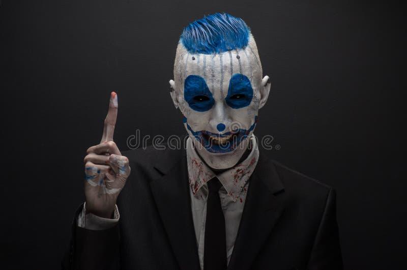 Schrecklicher Clown und Halloween-Thema: Verrückter blauer Clown im schwarzen Anzug lokalisiert auf einem dunklen Hintergrund im  lizenzfreie stockfotografie