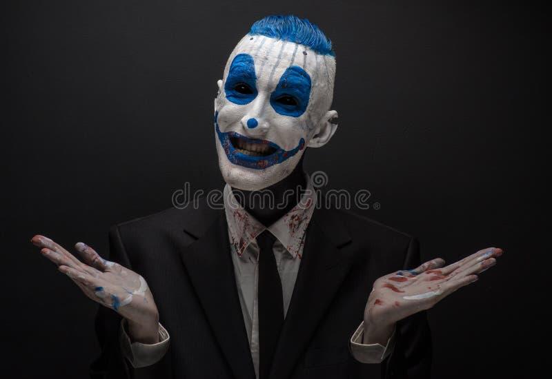 Schrecklicher Clown und Halloween-Thema: Verrückter blauer Clown im schwarzen Anzug lokalisiert auf einem dunklen Hintergrund im  stockfotos
