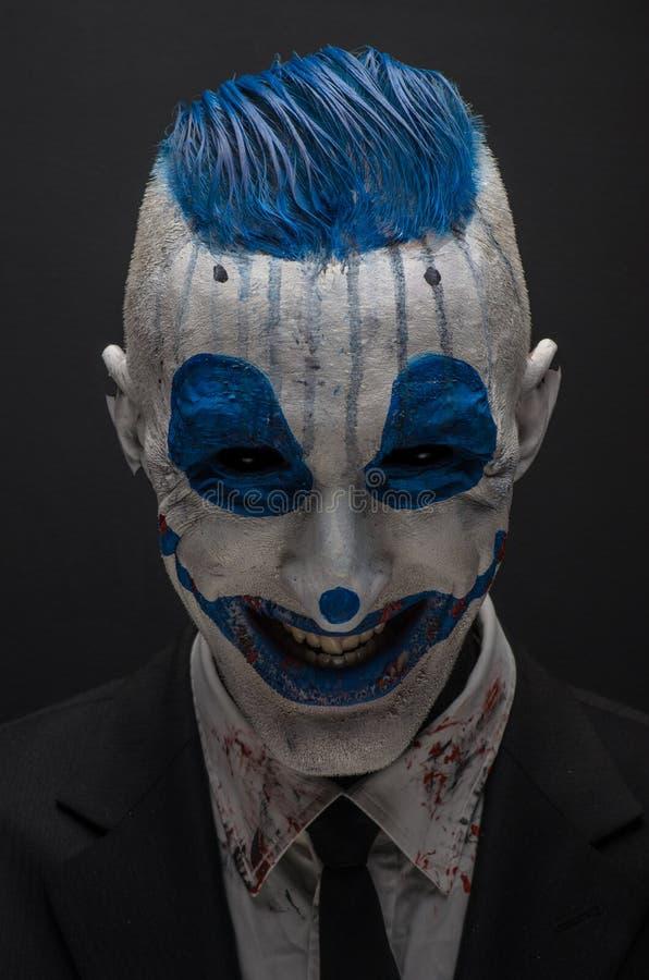 Schrecklicher Clown und Halloween-Thema: Verrückter blauer Clown im schwarzen Anzug lokalisiert auf einem dunklen Hintergrund im  lizenzfreies stockfoto