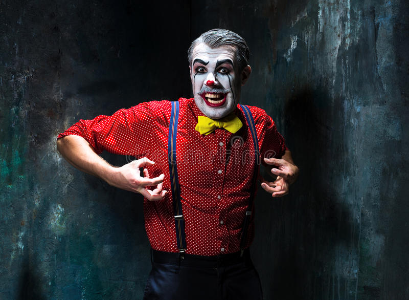 Schrecklicher Clown und Halloween-Thema: Verrückter roter Clown in einem Hemd mit Hosenträgern stockfotografie