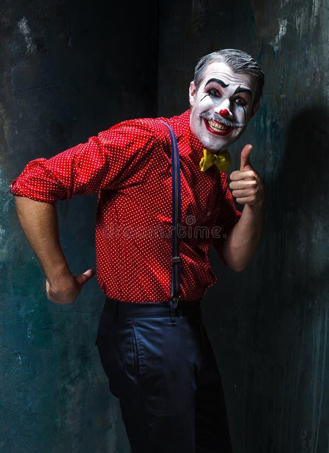 Schrecklicher Clown und Halloween-Thema: Verrückter roter Clown in einem Hemd mit Hosenträgern lizenzfreie stockfotografie