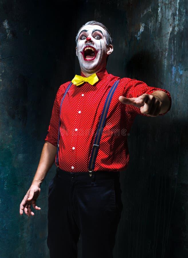 Schrecklicher Clown und Halloween-Thema: Verrückter roter Clown in einem Hemd mit Hosenträgern stockbild